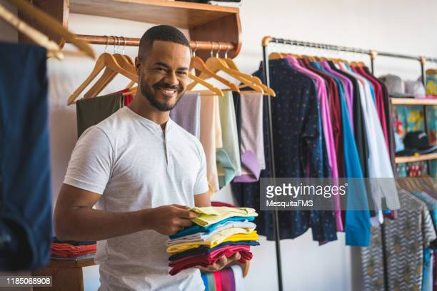 portrait of afro man in the clothing store - garment stock pictures, royalty-free photos & images