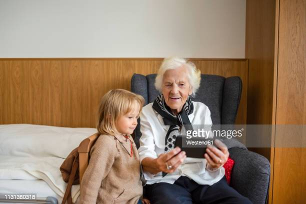 portrait of aged woman watching together with her great-granddaughter photos on smartphone - great granddaughter stock photos and pictures