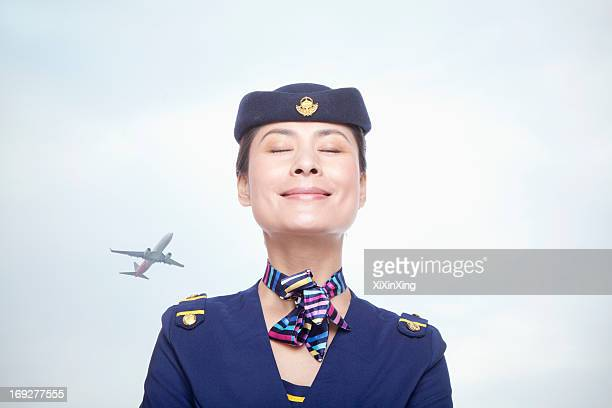 Portrait of air stewardess, eyes closed