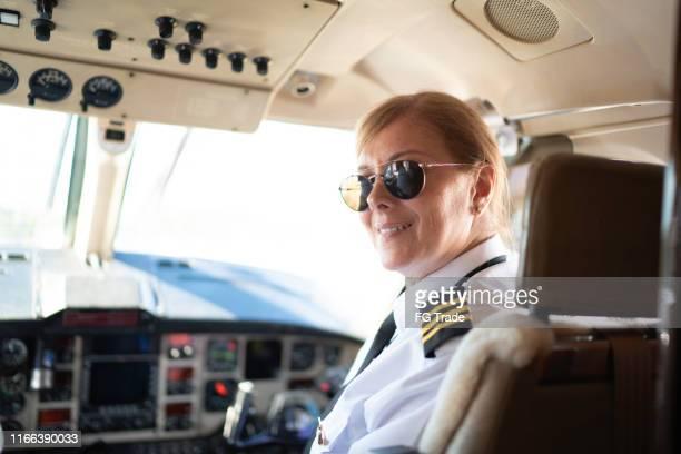 porträt des flugzeugpiloten, der in einem privatjet über die schulter schaut - pilot stock-fotos und bilder