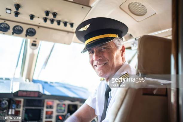 portrait of airplane pilot looking over shoulder in a private jet - commercial aircraft stock pictures, royalty-free photos & images