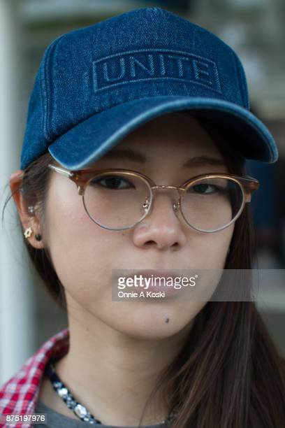 Portrait of Aki wearing half framed horn rimmed brown glasses and a denim blue baseball cap by Unite Aki stops for a quick fashion snap wearing a...