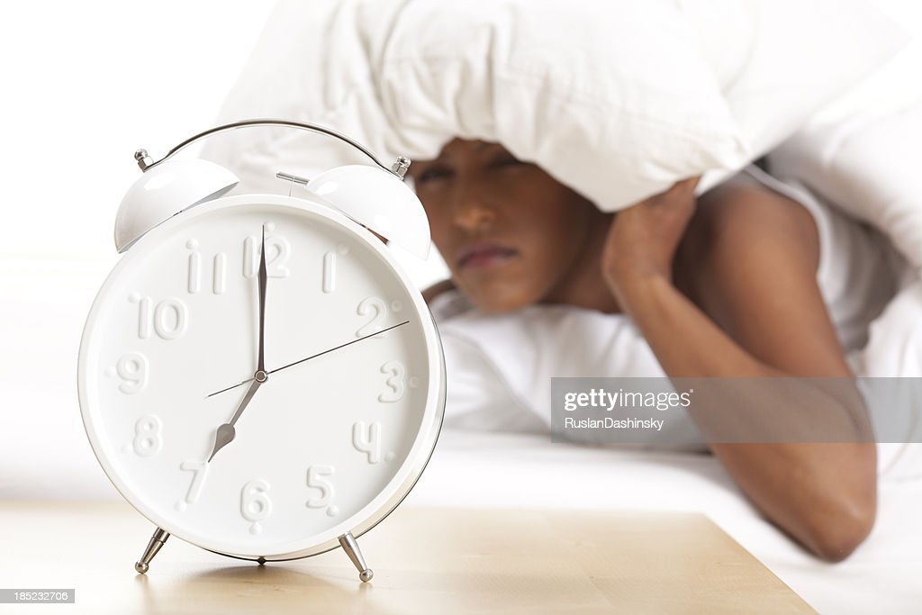 Portrait of alarm clock and upset woman in the background : Stock Photo