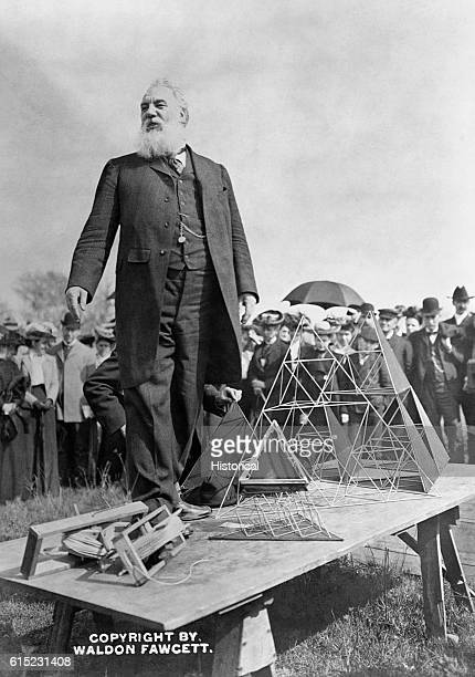 Portrait of Alexander Graham Bell inventor of the telephone He stands outdoors next to an elaborate kite