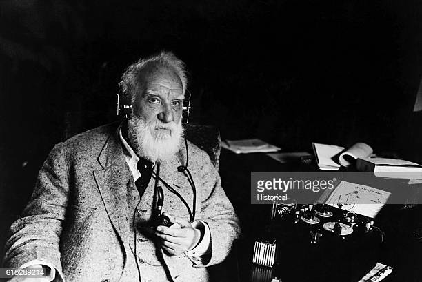 Portrait of Alexander Graham Bell inventor of the telephone He wears headphones that are attached to a piece of electrical apparatus