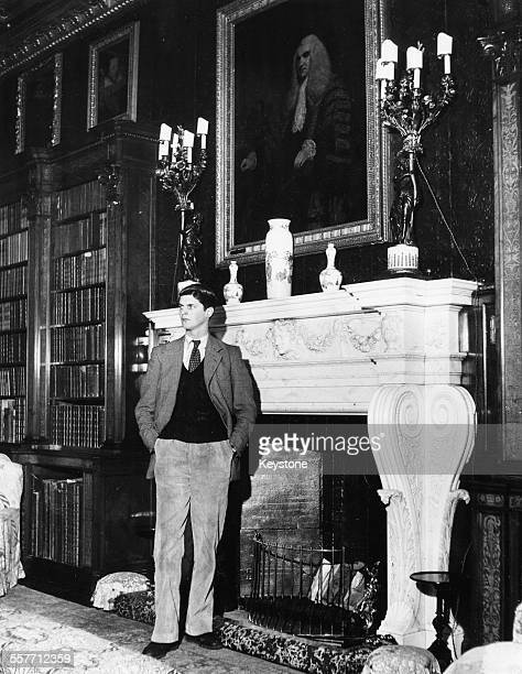 Portrait of Alexander Thynne 7th Marquess of Bath in front of his ornate fireplace Warminster England March 26th 1954
