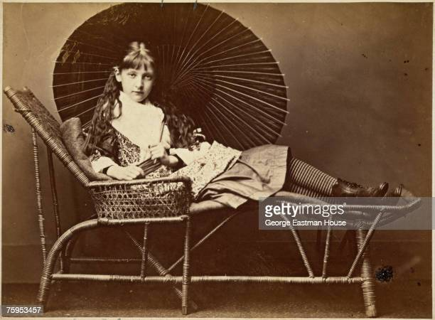 Portrait of Alexandra Rhoda Kitchin as she sits on a wicker deckchair and holds a parasol over her shoulder mid 1870s