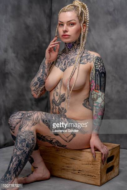 Portrait of Alicia Mecca as she sits on a wooden box, showing the tattoos on her neck, chest and torso, arms, and legs, New York, New York, June 21,...
