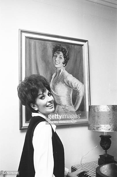 Portrait of Alma Cogan at home posing with a portrait of herself London circa 1964
