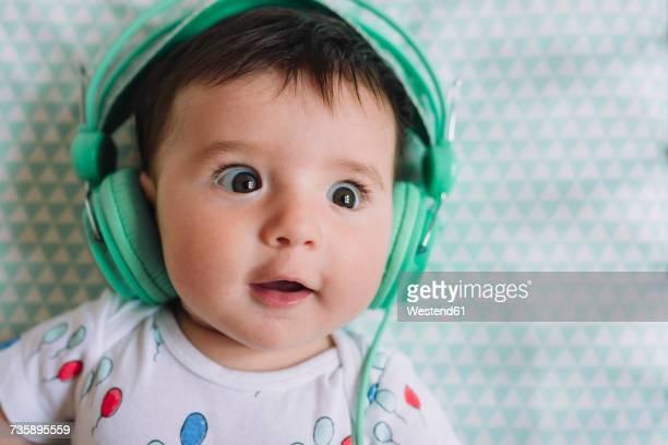 Portrait of amazed baby girl with headphones