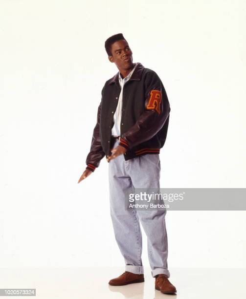 Portrait of American actor and comedian Chris Rock dressed in a varsity jacket and jeans New York 1993