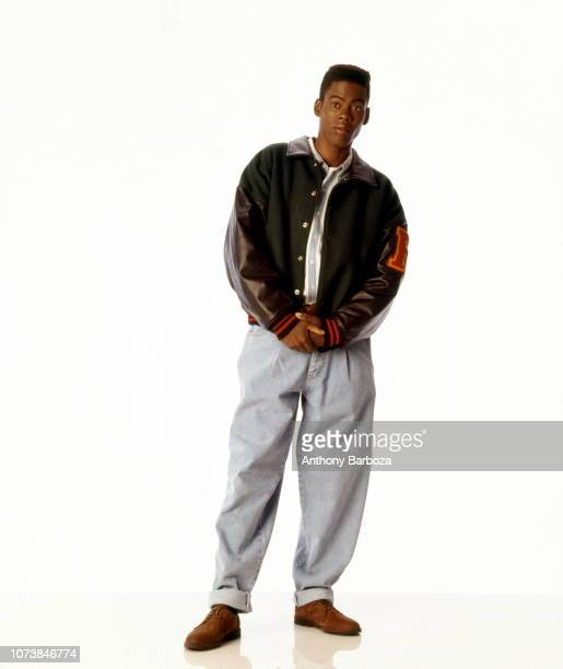 Portrait of American actor and comedian Chris Rock dressed in a varsity jacket and jeans as he poses in front of a white background Los Angeles...