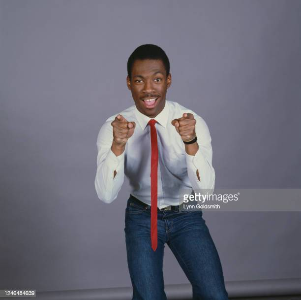 Portrait of American actor and comedian Eddie Murphy, dressed in jeans, a white shirt, and a red necktie, as he points his fingers at the camera,...
