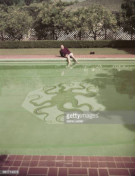 Portrait of American actor and comedian Jack Benny as he poses on the edge of his swimming pool circa 1956 The bottom of the pool features an octopus...
