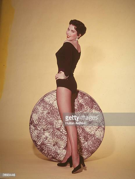 Portrait of American actor and dancer Ann Miller in a black leotard stockings and high heels as she looks back over her shoulder circa 1950s