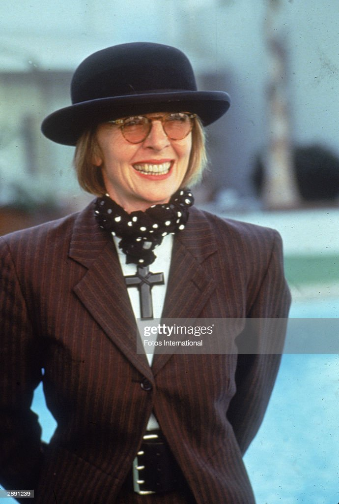Portrait of American actor and director Diane Keaton, 1996. She wears a purple & black striped suit coat, bowler hat, and, around her neck, a large black crucifix