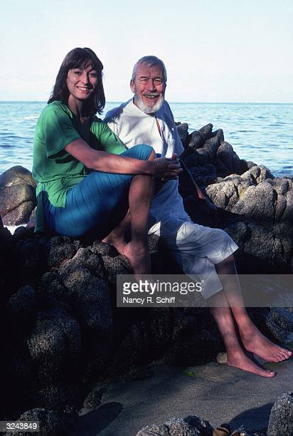 Portrait of American actor and director John Huston and his daughter American actor Anjelica Huston sitting on a rock formation by the seashore