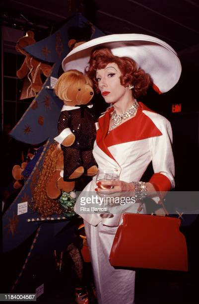 Portrait of American actor and drag artist John Epperson, in costume as his stage character Lypsinka, who poses with a teddy bear during an event at...