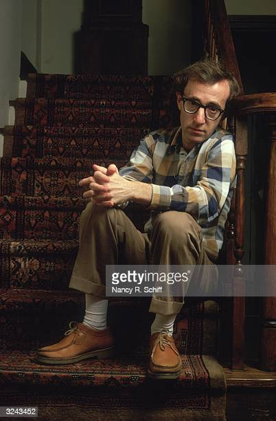 Portrait of American actor and film director Woody Allen sitting on a stairwell and leaning against a banister, with his hands clasped over one knee.