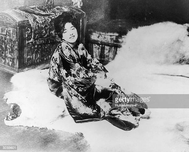 Portrait of American actor and model Evelyn Nesbit posing on a bearskin rug in a kimono