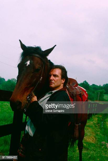 Portrait of American actor Armand Assante as he poses with a horse at his farm Campbell Hall New York 1996