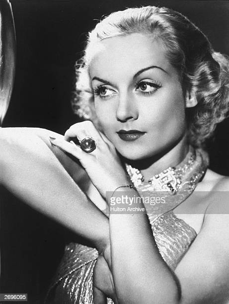 Portrait of American actor Carole Lombard looking to the side with one elbow propped up She wears an evening gown and a large ring