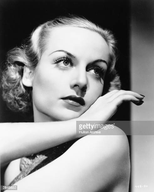 Portrait of American actor Carole Lombard resting her face on the back of her hand in a sleeveless gown circa 1930s