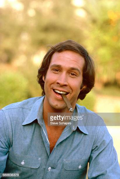 Portrait of American actor Chevy Chase as he poses with a cigar Los Angeles California 1974