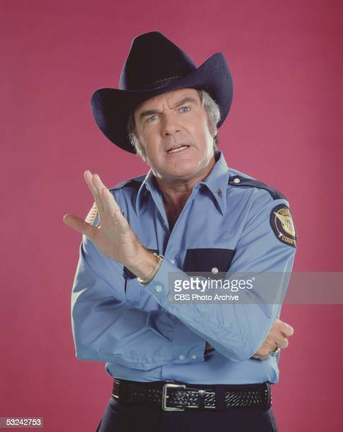 Portrait of American actor James Best wearing a uniform and making a beleaguered face as Sheriff Roscoe P. Coltrane on the television series 'The...