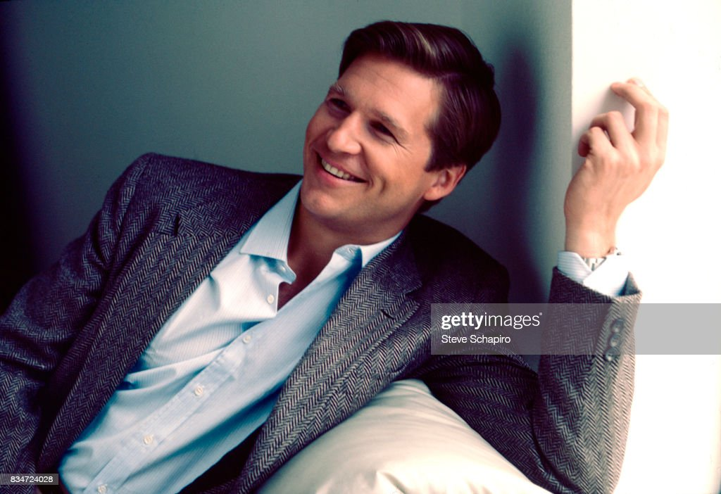 Portrait of American actor Jeff Bridges as he smiles, one arm over the back of a couch, Los Angeles, California, 1981.