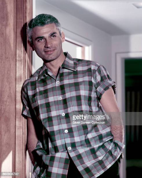 Portrait of American actor Jeff Chandler , hands in his pockets, as he leans in a doorway, 1950s.