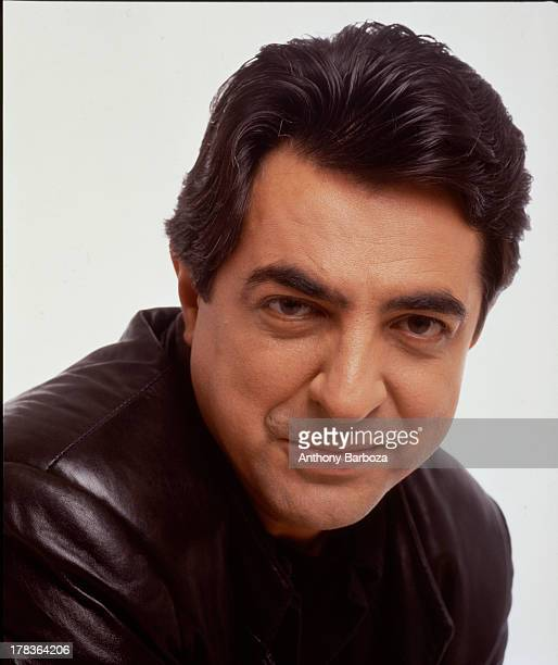 Portrait of American actor Joe Mantegna as he poses, dressed in a leather jacket, against a white background, 1991.
