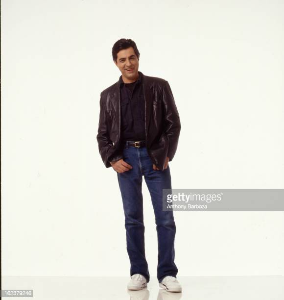 Portrait of American actor Joe Mantegna as he poses hands in his jeans pockets and dressed in a leather jacket as he poses against a white background...
