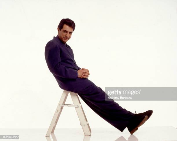 Portrait of American actor Joe Mantegna as he sits on a short step ladder, against a white background, 1991.