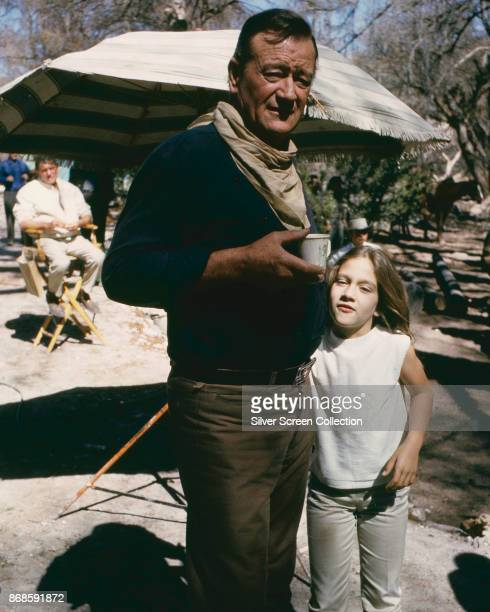 Portrait of American actor John Wayne as he poses with his daughter, Aissa, on the set of 'The Sons of Katie Elder' , 1965.