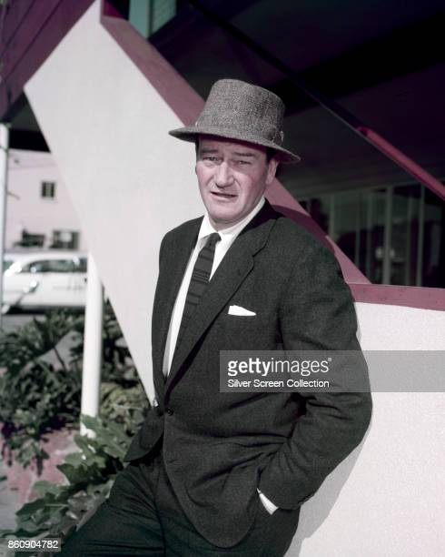 Portrait of American actor John Wayne dressed in a suit and hat hands in his pockets as leans against a low wall 1950s
