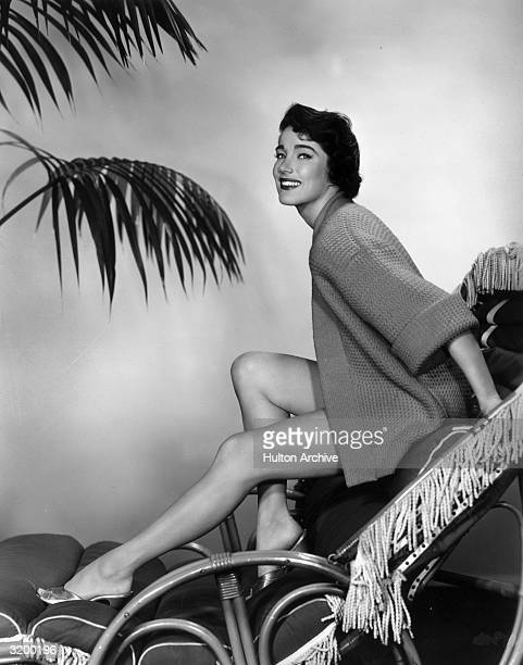 A portrait of American actor Julie Adams posing on a lounge chair in a cardigan and metallic mules with palm leaves in the background