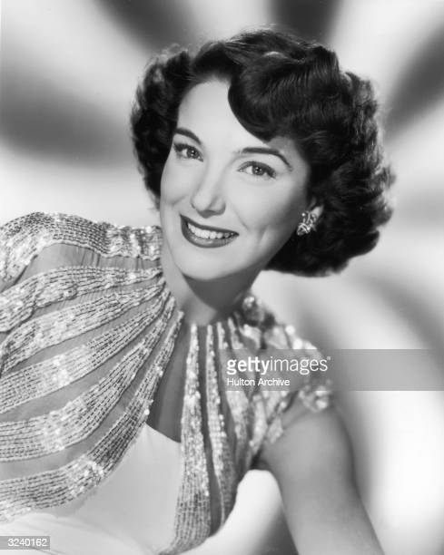 Portrait of American actor Julie Adams smiling in a sequined dress in a promotional portrait for the film 'Finders Keepers'