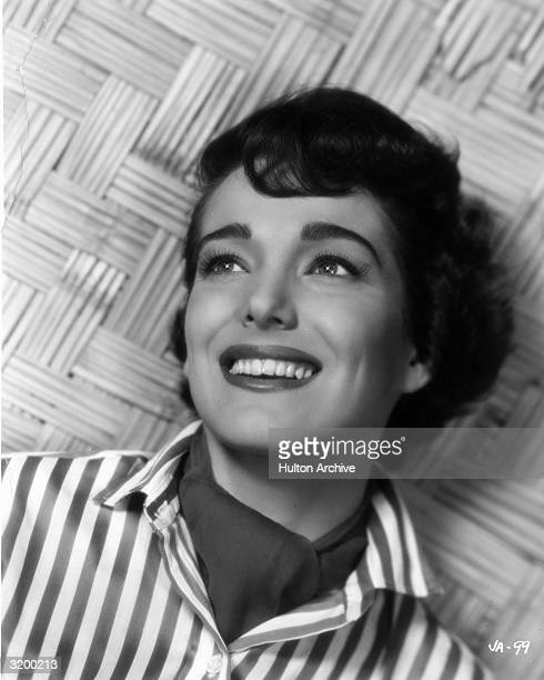 A portrait of American actor Julie Adams smiling while wearing a scarf tucked into a striped shirt
