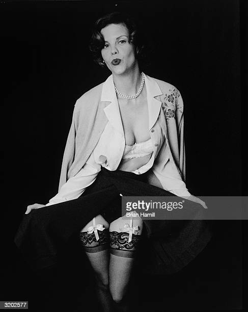 Portrait of American actor Kiersten Warren in a 1950sstyle costume consisting of pearls a blouse a cardigan and a pleated skirt wearing her blouse...