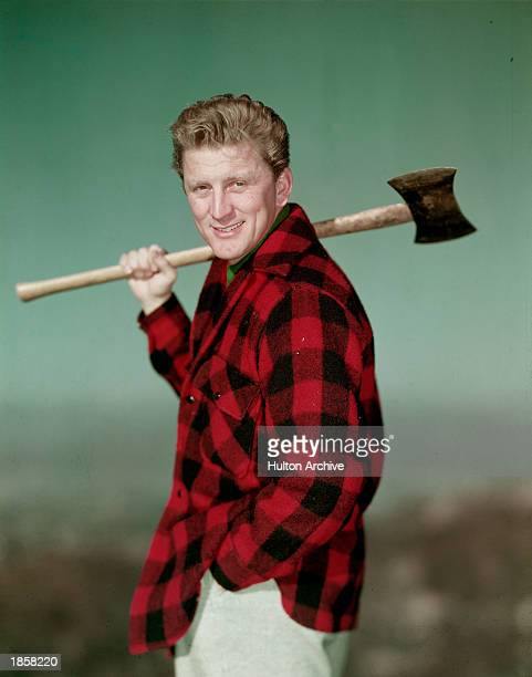 Portrait of American actor Kirk Douglas wearing a black and red checked jacket and holding an axe over his shoulder, 1950s.