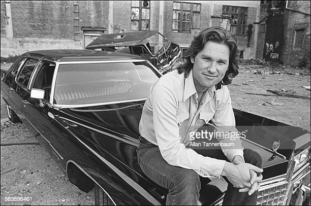 Portrait of American actor Kurt Russell as he sits on the hood of a Cadillac during the promotional tour for his film 'Escape From New York' New York...