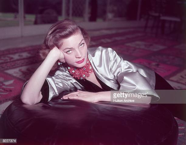 Portrait of American actor Lauren Bacall wearing a coral necklace and earrings and a gold satin jacket over a black velvet body suit seated on an...