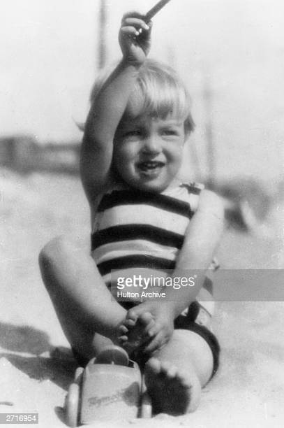 A portrait of American actor Marilyn Monroe as a young child playing on a beach in a striped bathing suit