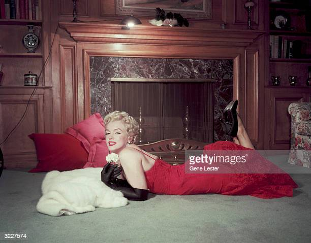 Portrait of American actor Marilyn Monroe as she holds a white carnation while lying on her stomach in front of a fireplace Monroe wears a red...