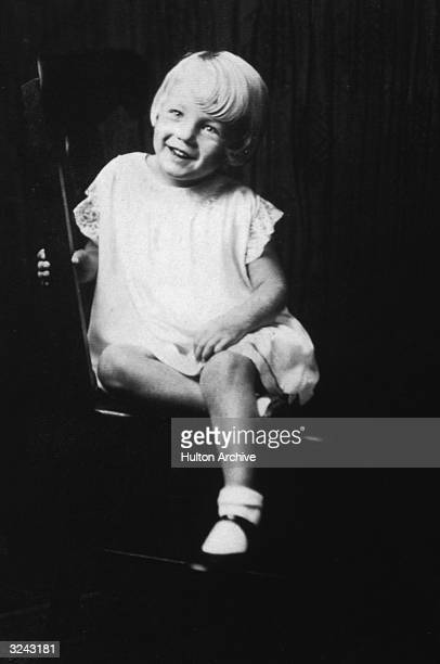 Portrait of American actor Marilyn Monroe at age 5 sitting in a wooden chair