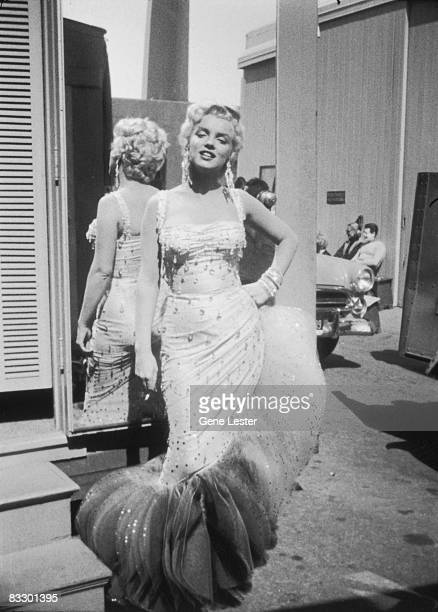 Portrait of American actor Marilyn Monroe in a lightcolored beaded gown as she stands with her back to a mirror a cigarette in one hand and the other...