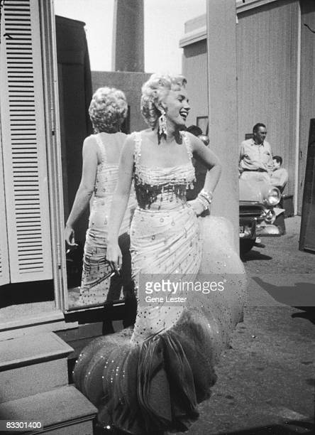 Portrait of American actor Marilyn Monroe in a lightcolored beaded gown as she laughs with her back to a mirror a cigarette in one hand and the other...