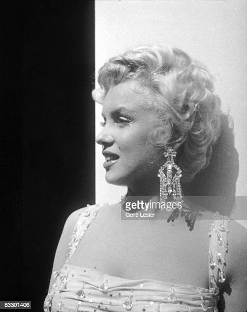 Portrait of American actor Marilyn Monroe in a lightcolored beaded gown as she leans against an open trailer door on the 20th Century Fox studios set...