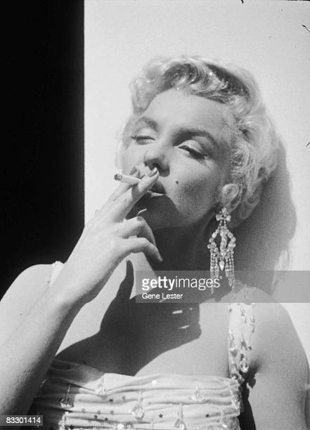 Portrait of American actor Marilyn Monroe in a lightcolored beaded gown smokes a cigarette as she leans against an open trailer door on the 20th...